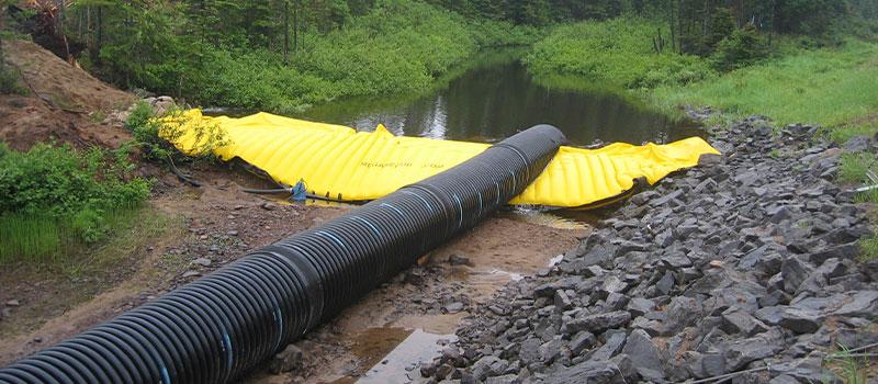 Nehirlerde çalışmak için esnek Water-Gate © batardoları. Boru hattı ile baypaslı çıkarılabilir baraj.