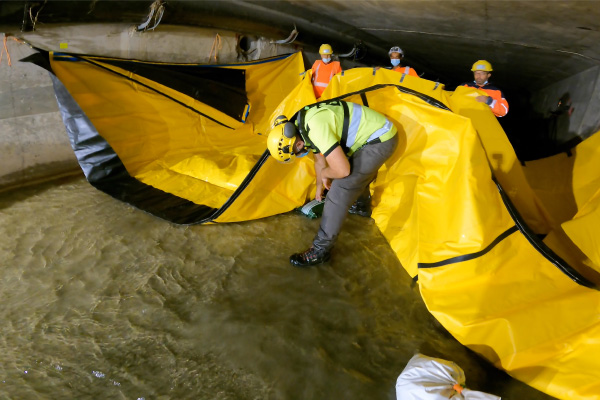 Sürtünme kuvvetlerini artırmak için Water-Gate © esnek barajının altına çakıl torbaları yerleştirin.